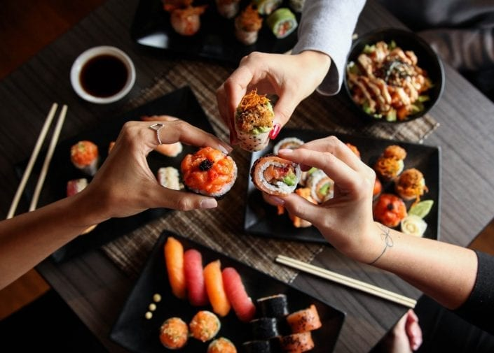 Three persons sharing plates of sushis