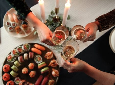 Celebration of friends around a table with sushi, candles and glass of wine.